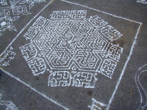 Kolam rangoli design with conch shells, flowers and elephants.